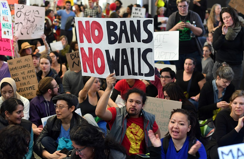 TOPSHOT - Protesters sit in the international terminal at San Francisco International Airport in San Francisco, California on January 29, 2017. US President Donald Trump issued an executive order yesterday barring citizens of seven Muslim-majority countries from entering the United States for the next 90 days and suspends the admission of all refugees for 120 days. / AFP PHOTO / Josh Edelson